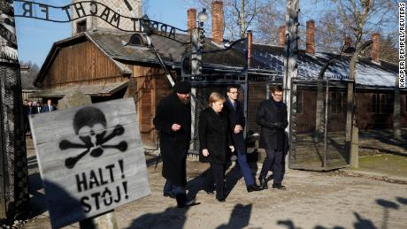"Merkel, Morawiecki and the Auschwitz museum director Piotr Cywinski walk past the ""Arbeit Macht Frei"" gate in the former Nazi death camp."