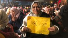 A woman holds a protest sign on December 27, 2019, at Shaheen Bagh, a neighborhood in the Indian capital of New Delhi where women have been staging a peaceful sit in.