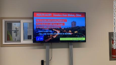A sign at the international arrivals area of Seattle-Tacoma International Airport instructs travelers coming from Wuhan, China, to watch for symptoms of coronavirus.