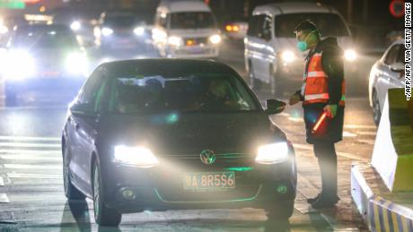 A staff member talks with a driver as he checks the body temperatures of passengers at an exit of a highway in Wuhan on Tuesday.