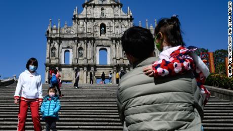 People wear protective masks when visiting Largo da Companhia de Jesus with the background of Ruínas de São Paulo in Macau on January 30, 2020.