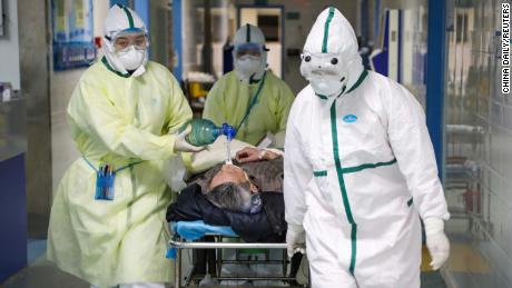 Health workers in protective suits move a patient to an isolated hospital ward in Wuhan on February 6.