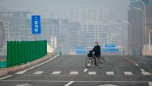 A man wearing a mask rides a bicycle along a deserted road in Beijing on February 12, 2020.