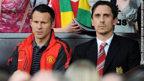 Giggs (left) and Neville (right) look on during the Premier League match between Manchester United and Fulham in 2011.