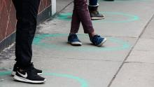 People stand in freshly painted circles, six-feet-apart, as they wait in a two-hour line on March 23, 2020 in Denver, Colorado.