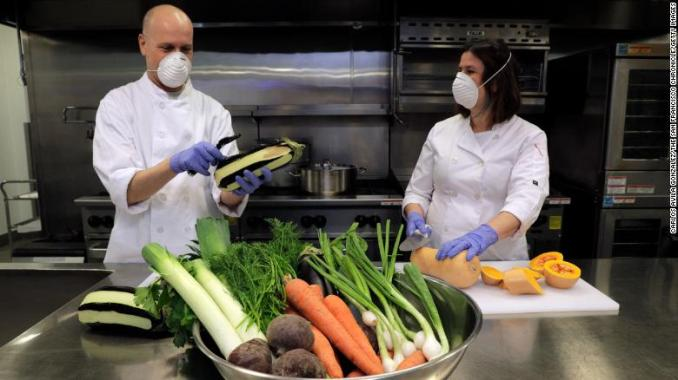 Caterer Aliza Grayevsky Somekh, right, and her husband Nadav Somekh prepare vegetables for takeaway Seder plates in the kitchen at Temple Beth Abraham in Oakland, California, on April 2, 2020.