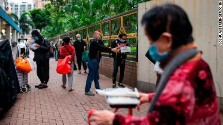 Chu Kin Lik, 61, makes sure people keep their distance while waiting for dinner at the Impact HK meal service on Tuesday, April 7