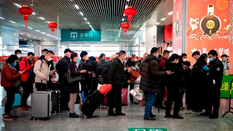 フェイスマスクをしている乗客が、温州の温州駅に到着したときに、電話で緑色のQRコードを携帯電話に表示してセキュリティを確保します。