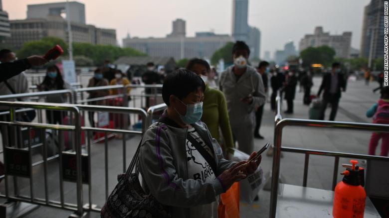 乗客は4月8日、武漢の漢口駅前で武漢健康法典を確認します。