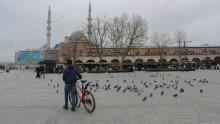 A man with his bike surrounded by pigeons in an almost empty Yenicami square at the Spice Bazaar in Istanbul, Turkey, during the weekend lockout.