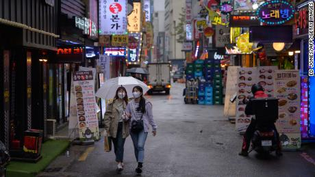Two women wear face masks in Seoul. Countries in which covering the face is a social norm generally fared better during the pandemic.
