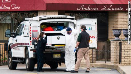 Medical workers put on masks and personal protective equipment while preparing to transport a body at Andover Subacute and Rehabilitation Center on April 16, 2020 in Andover, New Jersey. (Eduardo Munoz Alvarez/Getty Images)