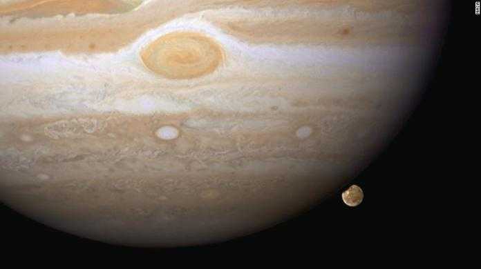 Hubble snapped this image in 2007 of Ganymede appearing to peek out from beneath Jupiter. Ganymede is the largest moon in our solar system, and it's even bigger than Mercury.