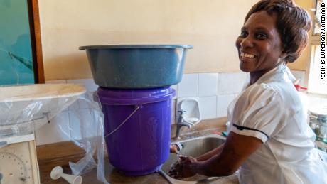 Patricia Mwenyeheri uses one of the two hand basins at the health center where she works.