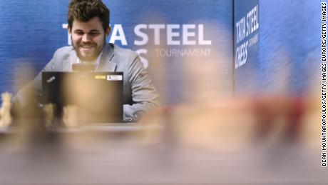 Carlsen speaks on his computer in the press room after he competes against Wesley So.