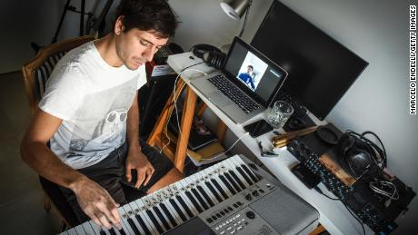 Musician Tati Diaz Bonilla plays the keyboard as a student listens and watches through Zoom during an online lesson from his apartment in Buenos Aires, Argentina.  (Marcelo Endelli/Getty Images)