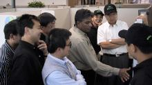 The WebEx team celebrates their IPO in 2000. WebEx cofounder Subrah Iyar, in a greige shirt, is flanked by Eric Yuan in a black polo shirt and hat. Yuan was an engineer for the company at the time. (Photo courtesy of Subrah Iyar)