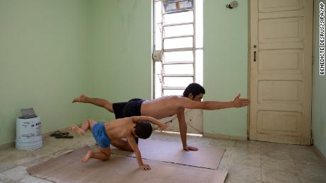 Photographer Bénédicte Desrus and his son Thiago  do yoga together during the pandemic in Mérida, Yucatán, Mexico.