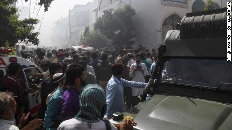 Rescue workers and bystanders gather near the site of the plane crash in Karachi on Friday.