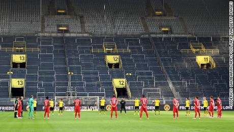 Players observe a minute of silence for the victims of the coronavirus before the German first division Bundesliga soccer match Borussia Dortmund and FC Bayern Munich.