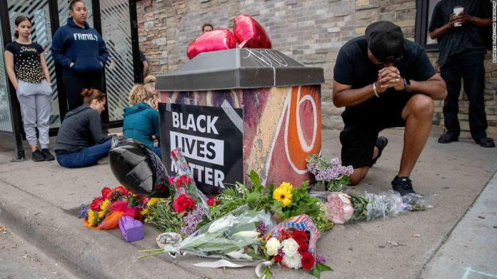 People gather and pray around a makeshift memorial in Minneapolis on May 26. It was near the site where Floyd was taken into police custody the previous day.