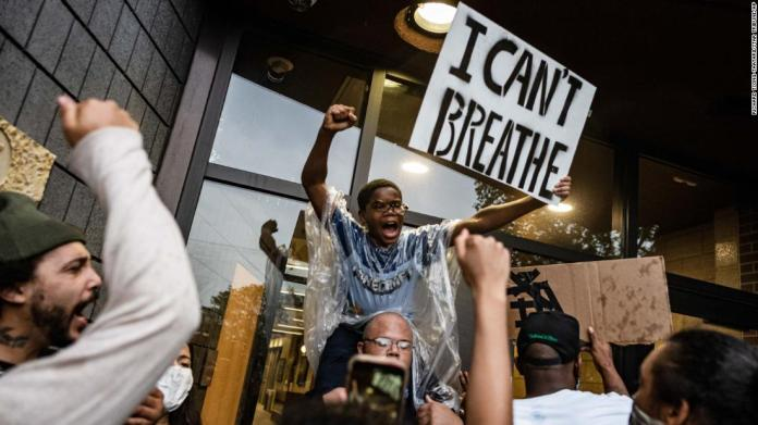 People gather outside a police precinct during demonstrations in Minneapolis on May 26.