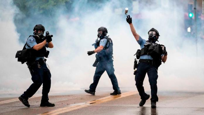 A police officer throws a tear-gas canister toward protesters during a rally in Minneapolis on May 27.