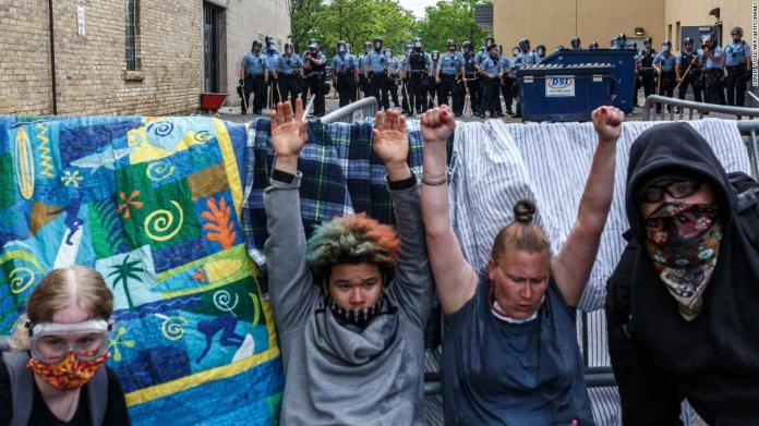 Protesters raise their hands up as they react to tear gas during a demonstration in Minneapolis on May 27.