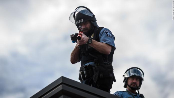 Two police officers stand on the roof of a Minneapolis police precinct during demonstrations on May 27.