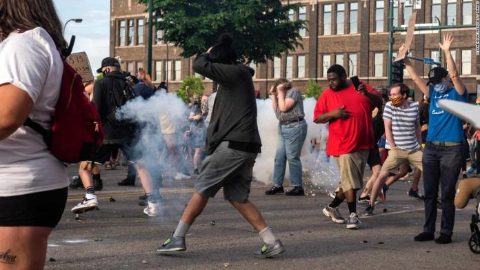 Minneapolis protesters react as a projectile launched by police explodes near them on May 27.