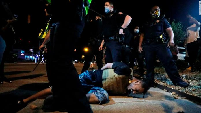 A protester in Memphis winces in pain after being hit with pepper spray by police on May 28.