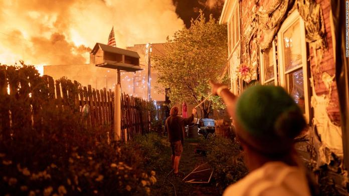 People use garden hoses and buckets to save homes in Minneapolis after rioters set fire to a housing complex under construction on May 27.