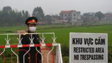 A Vietnamese People's Army officer stands next to a sign warning about the lockdown on the Son Loi commune in Vinh Phuc province on February 20.