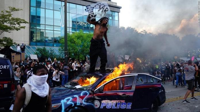 A man stands on top of a burning police car during a protest outside the CNN Center in Atlanta on May 29.