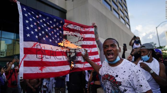 Protesters burn a flag outside the CNN Center in Atlanta on May 29.