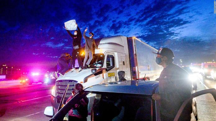 Demonstrators in Oakland climb atop a truck while blocking all lanes of traffic on Interstate 880 on May 29.