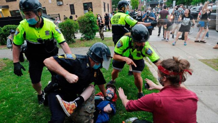 A police officer in Boston holds down a protester while another officer uses pepper spray on May 29.
