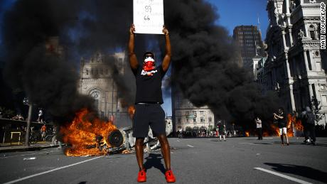 A man holds a sign when a fire sends large smoke in Philadelphia on Saturday.