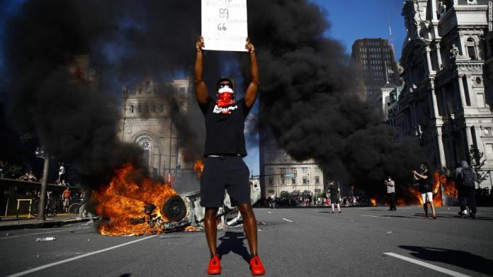 A protester holds a sign while a vehicle burns in a Philadelphia street on May 30.