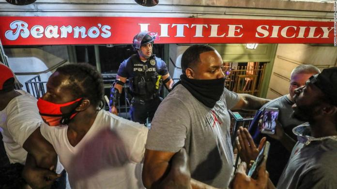 Protesters link arms and surround a police officer to protect him from the crowd in Louisville on May 28.