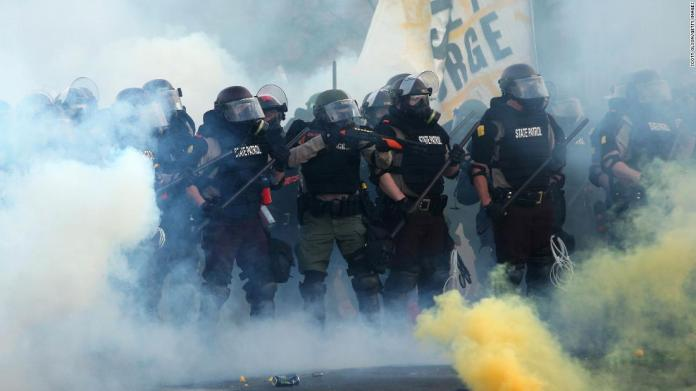 Police advance through smoke and tear gas in Minneapolis on May 30.
