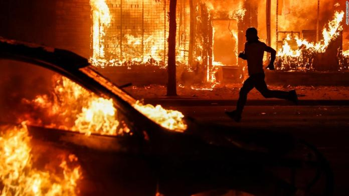 A protester runs past burning cars and buildings in St. Paul on May 30.