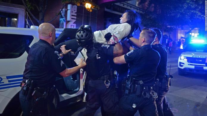 A woman is carried by police in Charlotte, North Carolina, on May 31.