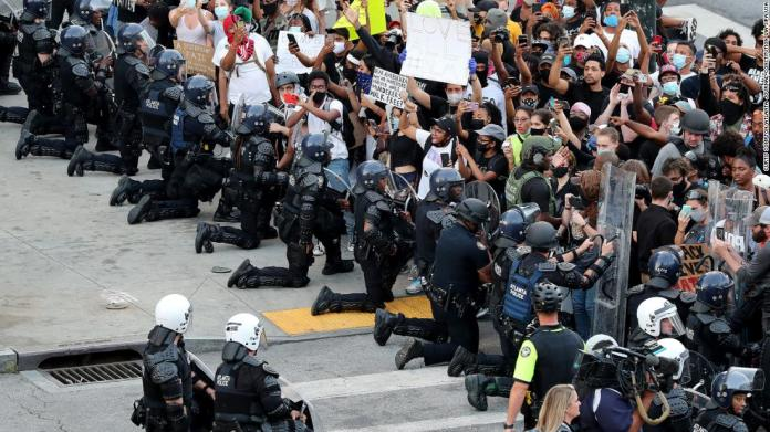 Law enforcement officers kneel with protesters in Atlanta on June 1.