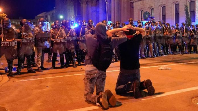 Two men kneel in front of a line of Kentucky state troopers during a protest in Louisville on June 1.