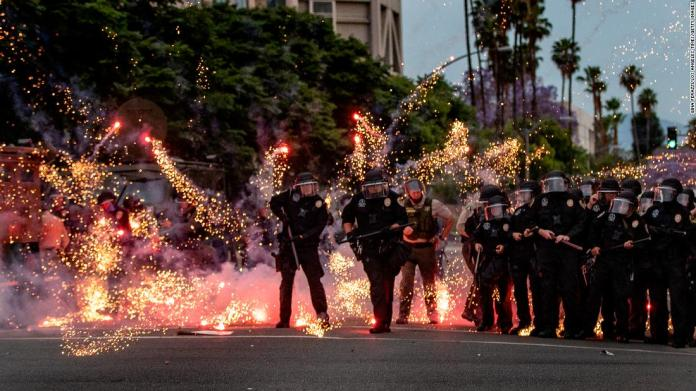 A firework thrown by a protester explodes at the feet of police in Riverside, California, on June 1.