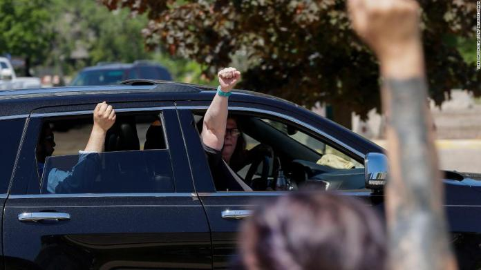 Passengers hold up their fists in solidarity with protesters as they drive by the Wood County Courthouse in Wisconsin Rapids, Wisconsin, on June 2.