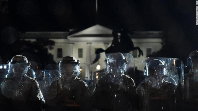 Police officers hold a perimeter June 2 behind a metal fence that was recently erected in front of the White House.