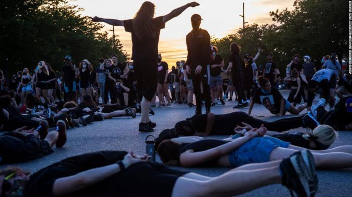 Protesters lie down in an intersection, blocking traffic in Coralville, Iowa, on June 2.