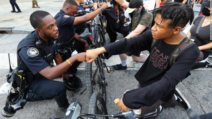Atlanta Police Officer J. Coleman shares a fist bump with protester Elijah Raffington on June 3. The police bicycle unit was taking a knee with protesters outside the CNN Center.